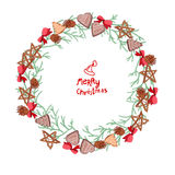 Round Christmas wreath with fir branches and cookies  on white. Royalty Free Stock Photo