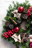 Round Christmas wreath with red baubles and berries. Closeup of home made, hand made round Christmas wreath with red baubles and berries- detail Royalty Free Stock Image