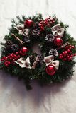 Round Christmas wreath with red baubles and berries. Closeup of home made, hand made round Christmas wreath with red baubles and berries- detail Stock Photos