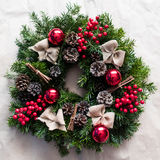 Round Christmas wreath with red baubles and berries. Closeup of home made, hand made round Christmas wreath with red baubles and berries- square crop Royalty Free Stock Image