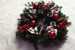 Round Christmas wreath with red baubles and berries. Home made, hand made round Christmas wreath with red baubles and berries- closeup in natural light Stock Image
