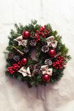 Round Christmas wreath with red baubles and berries. Home made, hand made round Christmas wreath with red baubles and berries- closeup, in natural light Royalty Free Stock Images