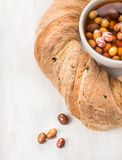 Round Ciabatta bread with olives on white wooden Royalty Free Stock Images