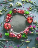 Round circle frame of homemade red berries fruits ice cream or Popsicle in plate on kitchen table background with garden flowers a. Nd ingredients, top view stock photos