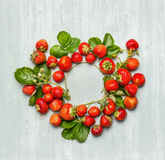 Round circle frame of  strawberries with green leaves and flowers on wooden background, top view Stock Photos