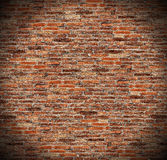 Round circle spotlight on red brick wall, radial gradient shadow on old dark brown, orange brick fences. Grungy rusty blocks of stone work for texture and Royalty Free Stock Photo