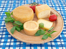 Round, circular cheeseboard with cheese on blue tablecloth. Stock Photos