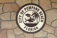 Round City of Pompano Beach Sign. Pompano Beach, FL, USA - February 12, 2014: One brown and beige round City of Pompano Beach sign on a stone wall of the Royalty Free Stock Photography