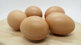 Many Chicken Brown Eggs on the Chopping board with white background. Round clear skin Chicken Brown Eggs on the chopping board with white isolate background Stock Photos