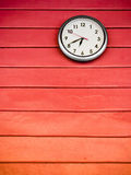Round clock on red wall Stock Photography