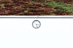 Round clock on a white wall Stock Images