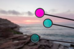 Round colored glass with rugged coastline in the background during dusk royalty free stock photos