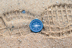 Round compass on sand footmark. Background Stock Photos