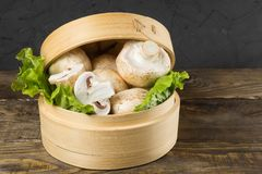Round container with lettuce leaves and mushrooms on wooden table. Round container with lettuce leaves and mushrooms on a table Stock Photos