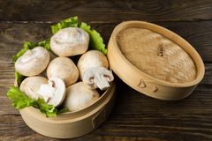 Round container with lettuce leaves and mushrooms on wooden table. Round container with lettuce leaves and mushrooms on a table Royalty Free Stock Photos