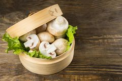 Round container with lettuce leaves and mushrooms on wooden table. Round container with lettuce leaves and mushrooms on a table Stock Images