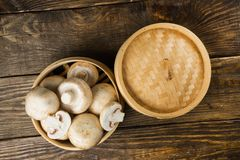 A round container of white mushrooms on wooden table. Top view. A round container of white mushrooms on table Royalty Free Stock Photos