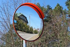 A round convex mirror is installed at the village crossroads for. Safety. Sunny spring day landscape royalty free stock photography