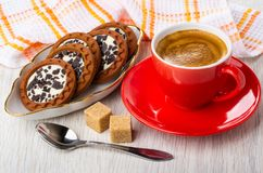 Cookies with cream, chocolate in plate, coffee in red cup on saucer, sugar, spoon, napkin on table. Round cookies with cream and chocolate in white plate, coffee royalty free stock photos