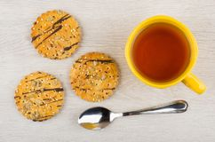 Round cookies with sunflower seeds, sesame, teaspoon, cup of tea. Round cookies with sunflower seeds, sesame, teaspoon and cup of tea on wooden table. Top view Stock Photography