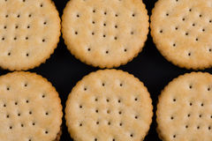 Round crackers in rows against black background Stock Photography