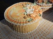 Round cream-coloured handicraft paper box decorated with flowers. Round cream-coloured wickerwork box from paper decorated with flowers stock photos