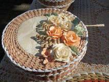 Round cream-coloured handicraft paper box decorated with roses. Round cream-coloured wickerwork box from paper decorated with roses royalty free stock photos