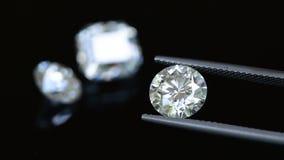 Diamond in tweezers. Round cut diamond brilliance. Diamond in tweezers stock video