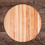 Round cutting board on an old table Stock Photo
