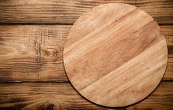 Round cutting board on old wooden burned table or board for back Stock Images