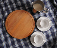 Round cutting board, a pitcher of milk and cups on blue plaid tablecloth with place for design. Round wooden cutting board, a pitcher of milk and two white cups Stock Image