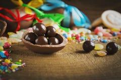 Round czekoladowi cukierki w czekoladowym jajku Zdjęcia Stock