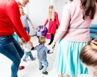 Round dance in the kindergarten. Round dance moms and children. Moms and their children hold hands by forming a circle in the kindergarten royalty free stock image