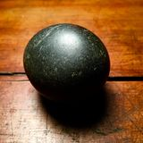 Round dark stone on scarred wood. Dark charcoal stone naturally polished by the elements, set against a glowing antique wood surface scarred by time. Zen stone royalty free stock photos