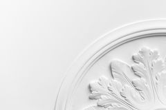 Round decorative clay stucco relief molding. With floral ornaments on white ceiling in abstract classical style interior Stock Image