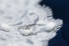 Diamond wedding ring on lace wedding dress stock photos