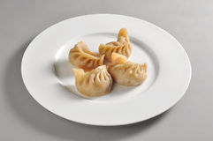Round dish with Chinese steamed ravioli Jiaozi. Isolated on grey background Royalty Free Stock Image