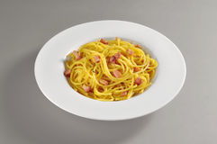 Round dish with a portion of spaghetti carbonara. On grey background Stock Photos