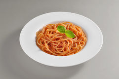 Round dish with a serving of spaghetti with tomato souce. Isolated on grey background Royalty Free Stock Photography