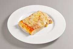 Round dish with square pizza piece. Round dish with square slice of pizza isolated on grey background stock photography
