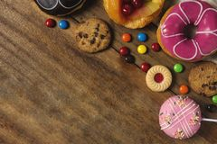 Round donuts, cookies, and fruitcake, flat lay dessert on wooden table with candy stock photography