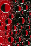 Round drops of water with highlights  on black and red glass. Round drops of water with highlights on a close-up on black and red glass Stock Image