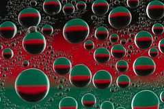 Round drops of water with highlights  on  black-red-green glass. Round drops of water with highlights on a close-up on a black-red-green glass Stock Photos