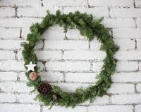 Round elegant Christmas wreath hanging on white brick wall Royalty Free Stock Images