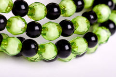 Round facet beads. Green and black facet beads royalty free stock photography