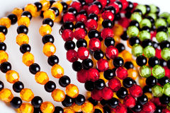 Round facet beads. Green, yellow, red and black facet beads stock image