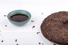 Round flat disc of puer tea and cup on white royalty free stock photos