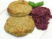 Round flat potato dough cakes with red cabbage stock photography