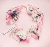 Round floral frame arrangement with pastel pink flowers, markers and ribbon royalty free stock photography