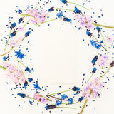 Round floral frame blue and pink flowers and card on white background. Flat lay, top view. Blog, social media or website backgroun royalty free stock photo
